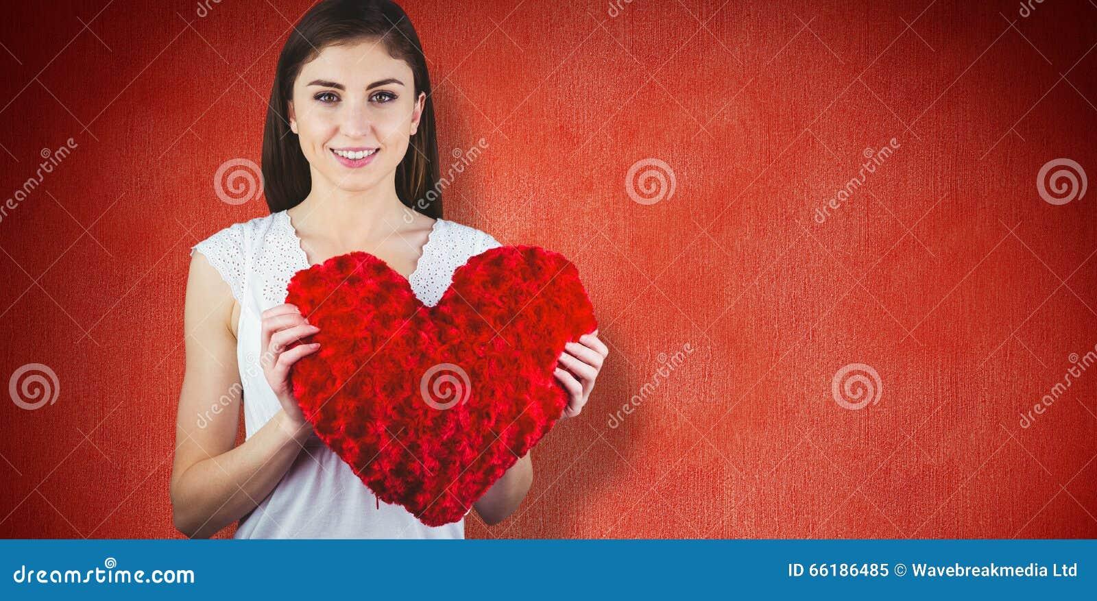 Sammansatt bild av för hjärtaform för kvinna den hållande kudden