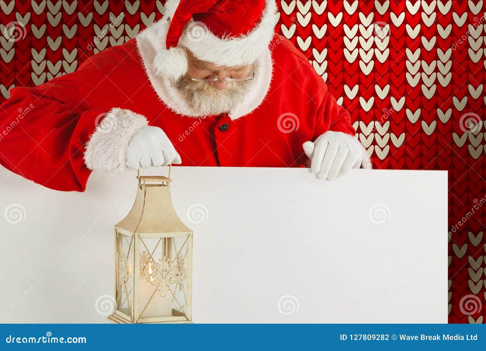 Sammansatt bild av Santa Claus den hållande jullyktan på det vita brädet