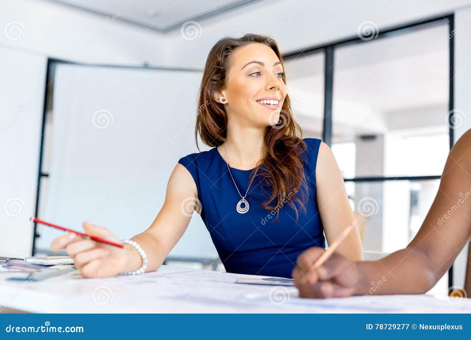 Sammanträde för ung kvinna på ett skrivbord i ett kontor och ett arbete på ritning
