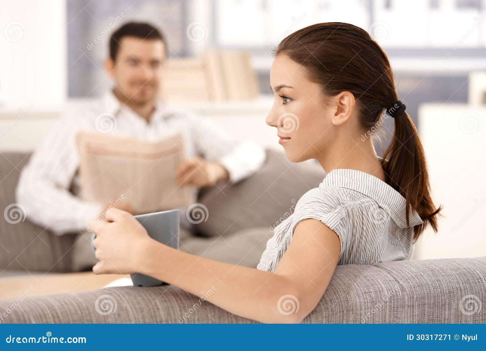 Sammanträde för ung kvinna på soffaman i bakgrund