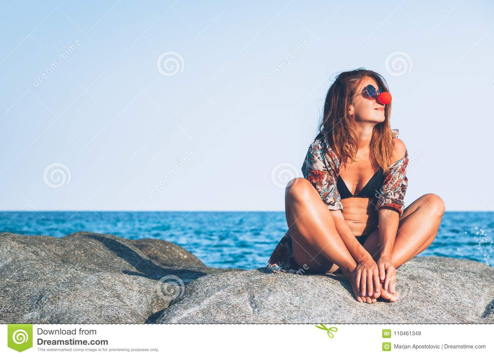 Sammanträde för ung kvinna på vagga som tycker om att solbada