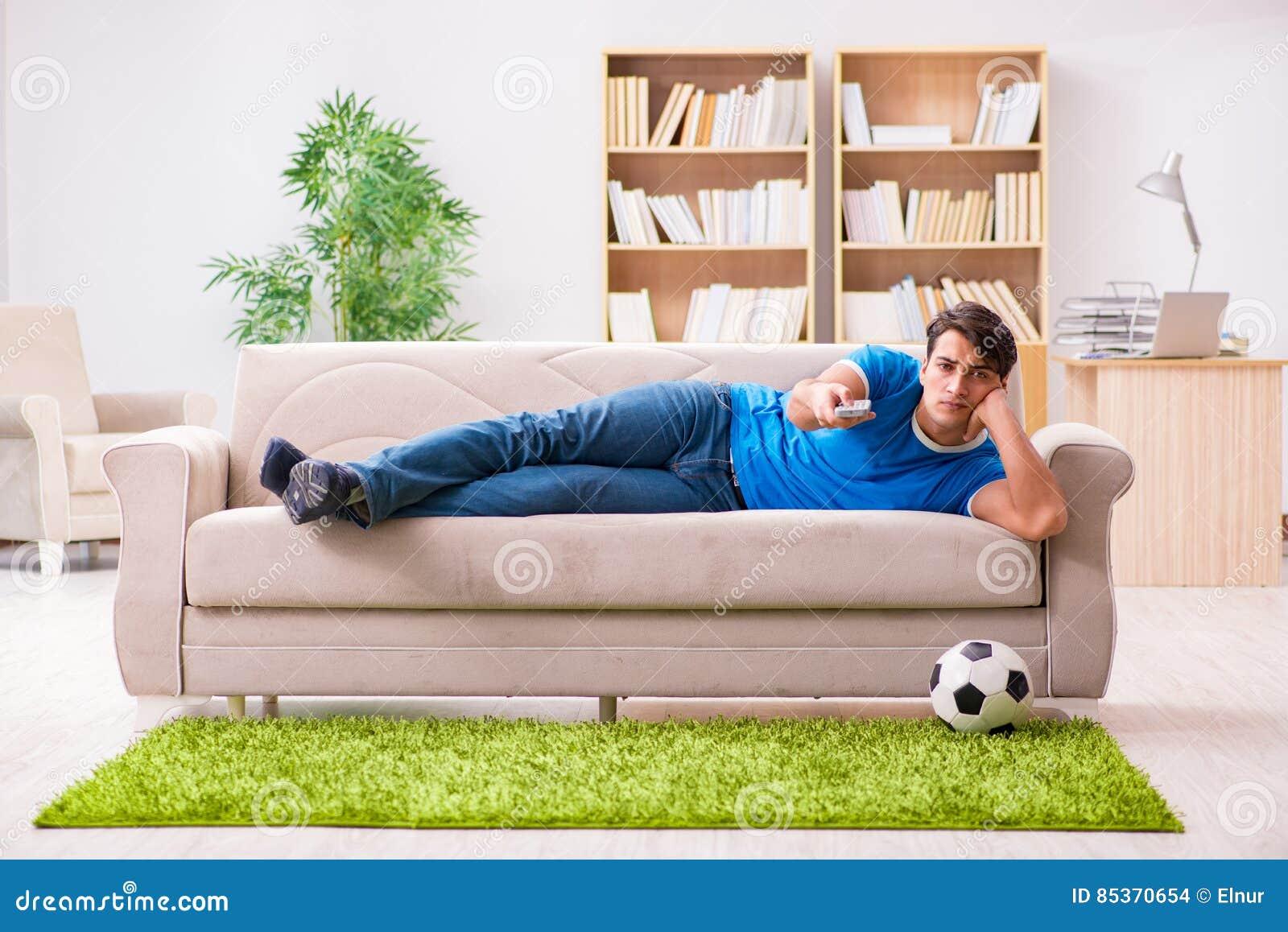 Sammanträdet för fotboll för man det hållande ögonen på hemmastadda i soffa