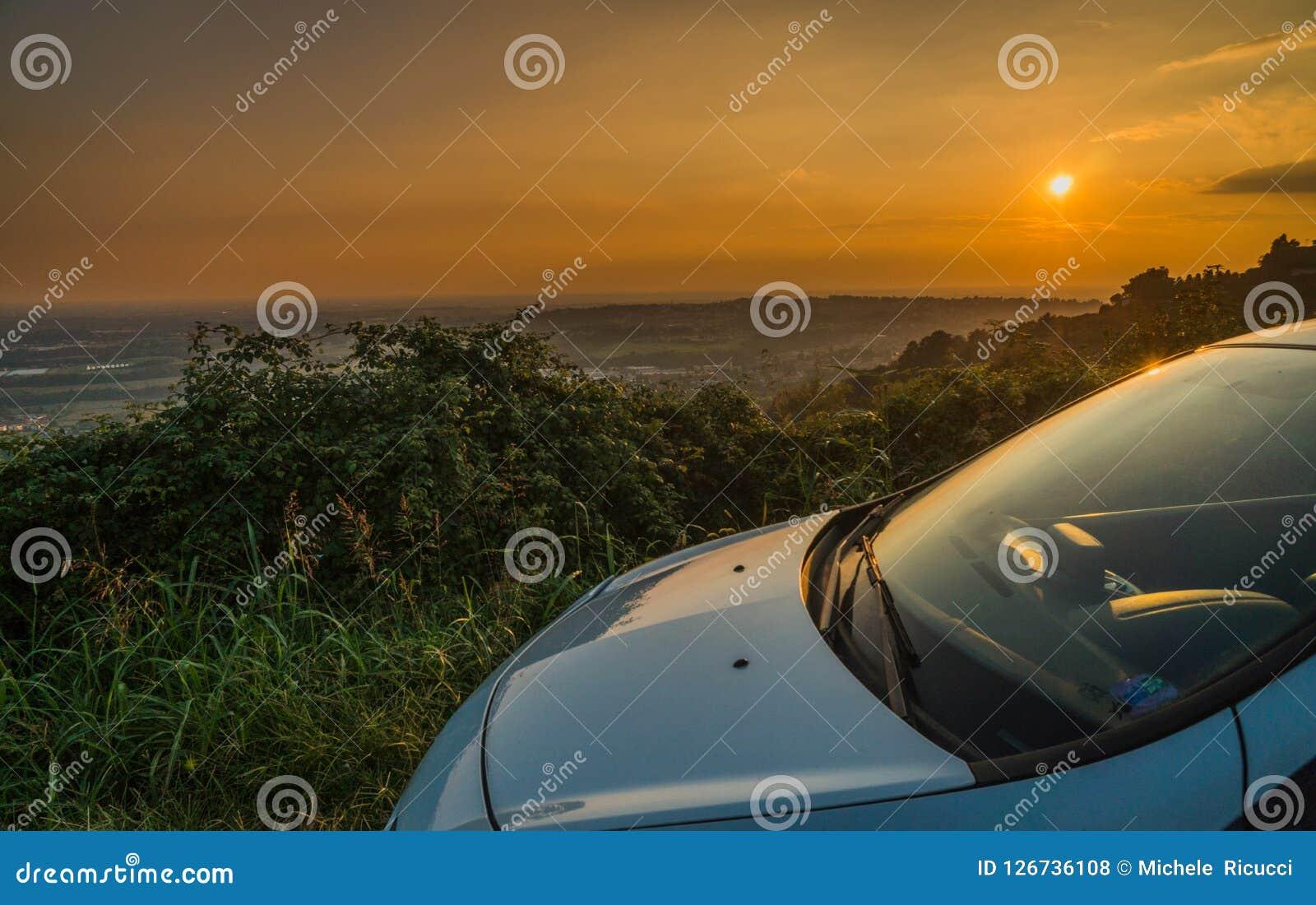 Samochód parkujący w ulicie z oszałamiająco widokiem przy zmierzchem