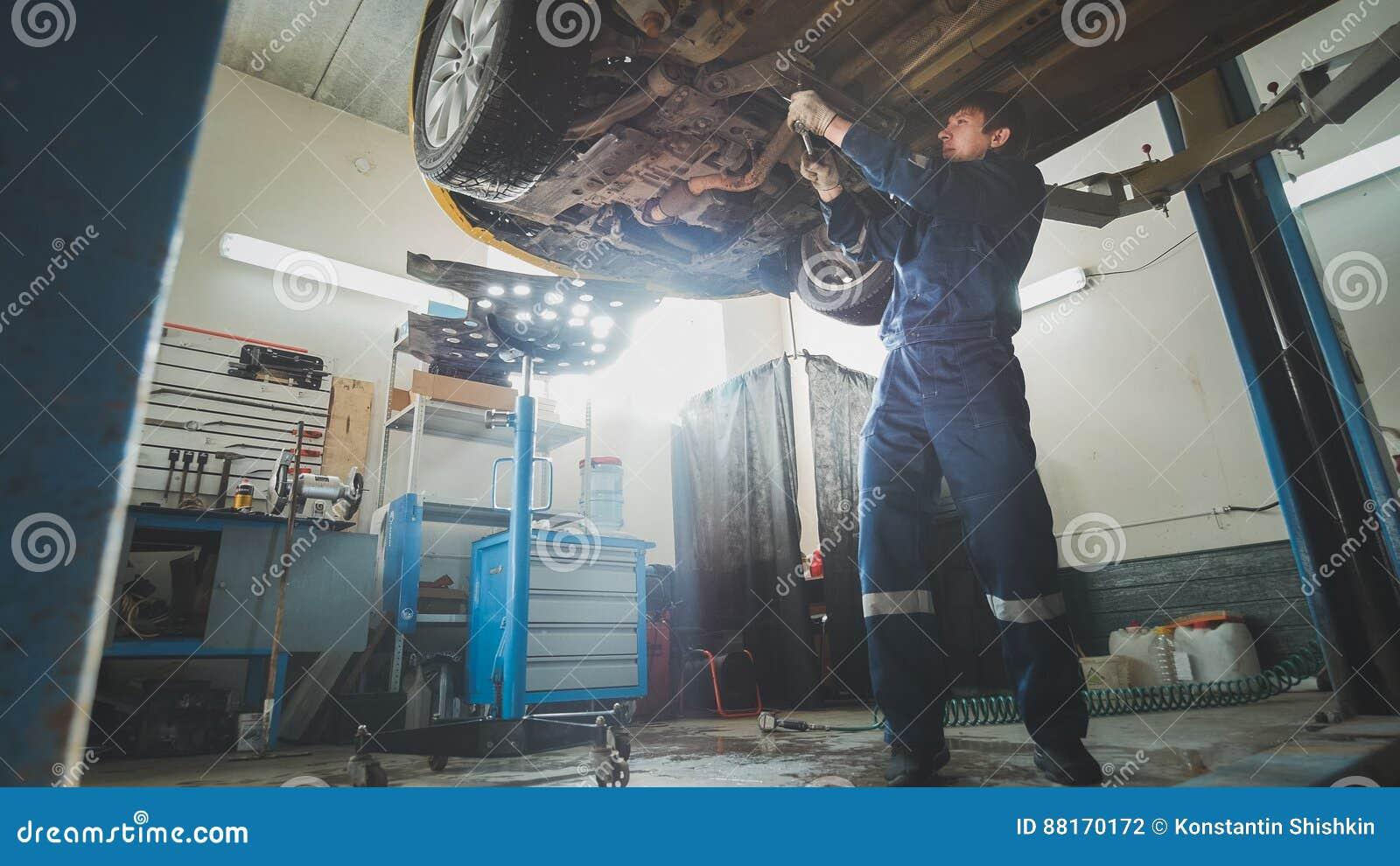 Samochód usługa - mechanik sprawdza zawieszenie samochód, szeroki kąt
