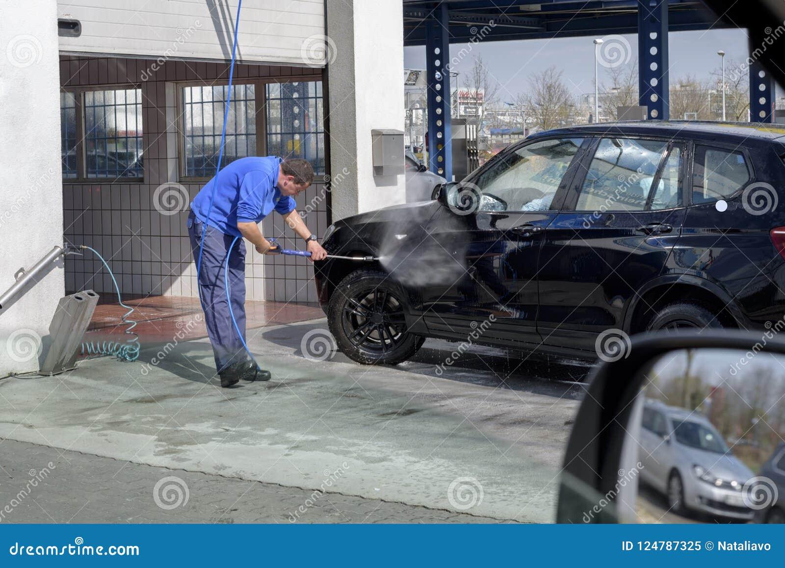 Samochodowa domycie stacja Mężczyzna pracownik myje samochodowych koła z wysokość naciska wodą