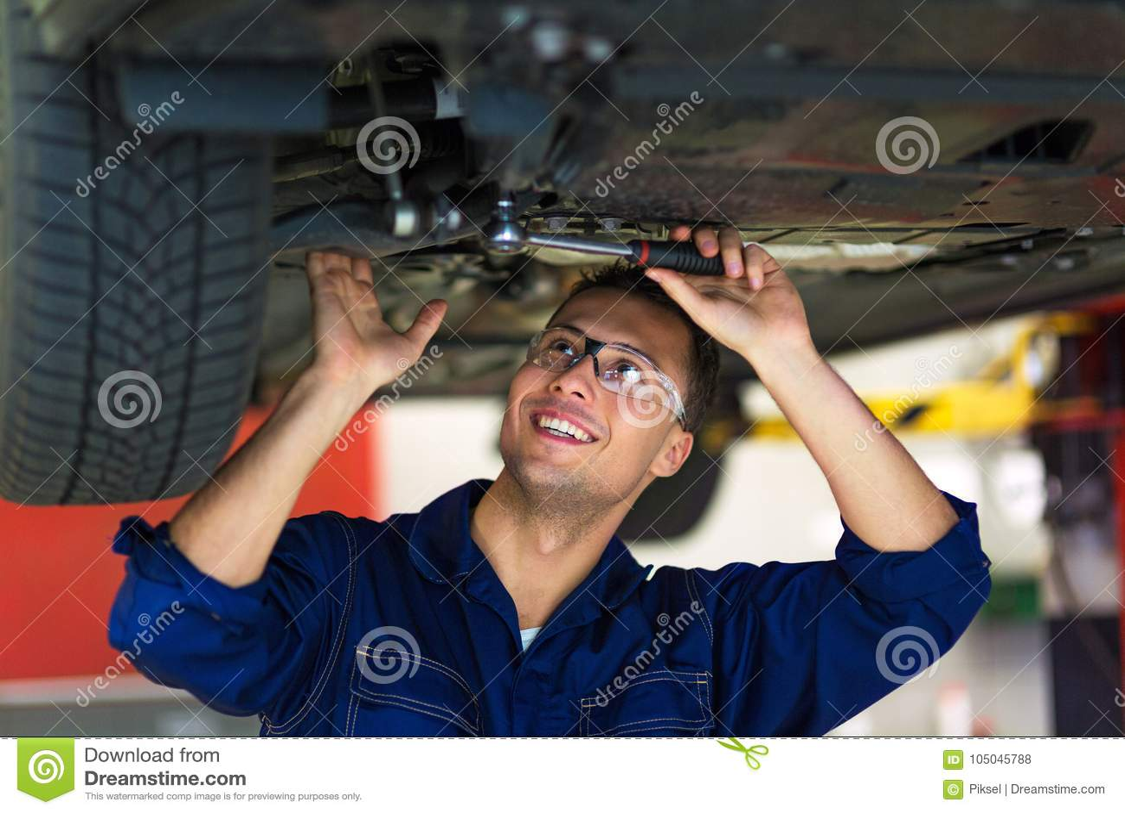 Samochodowy mechanik pracuje na spodzie samochód
