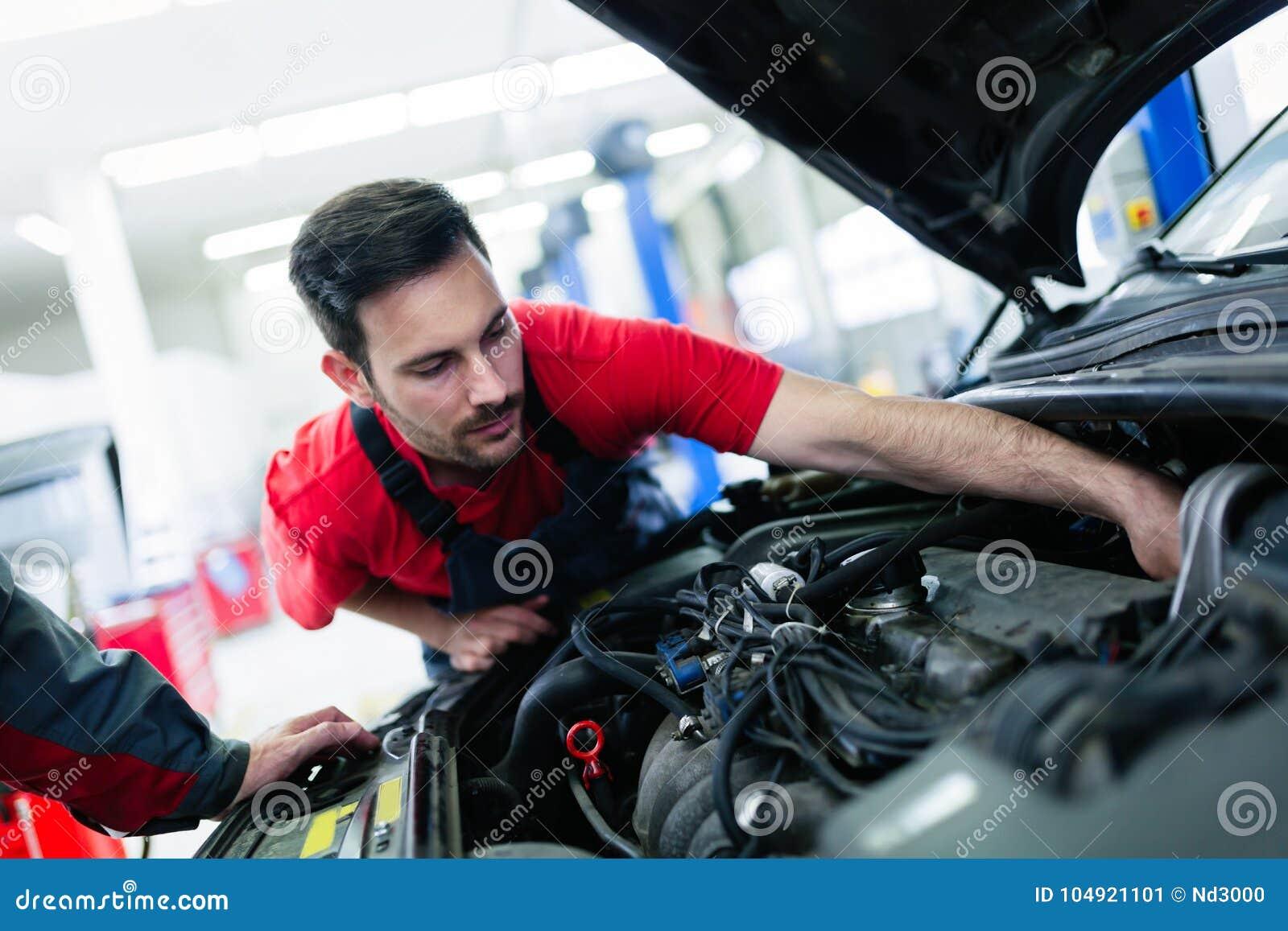 Samochodowy mechanik pracuje przy automobilowym usługowym centrum