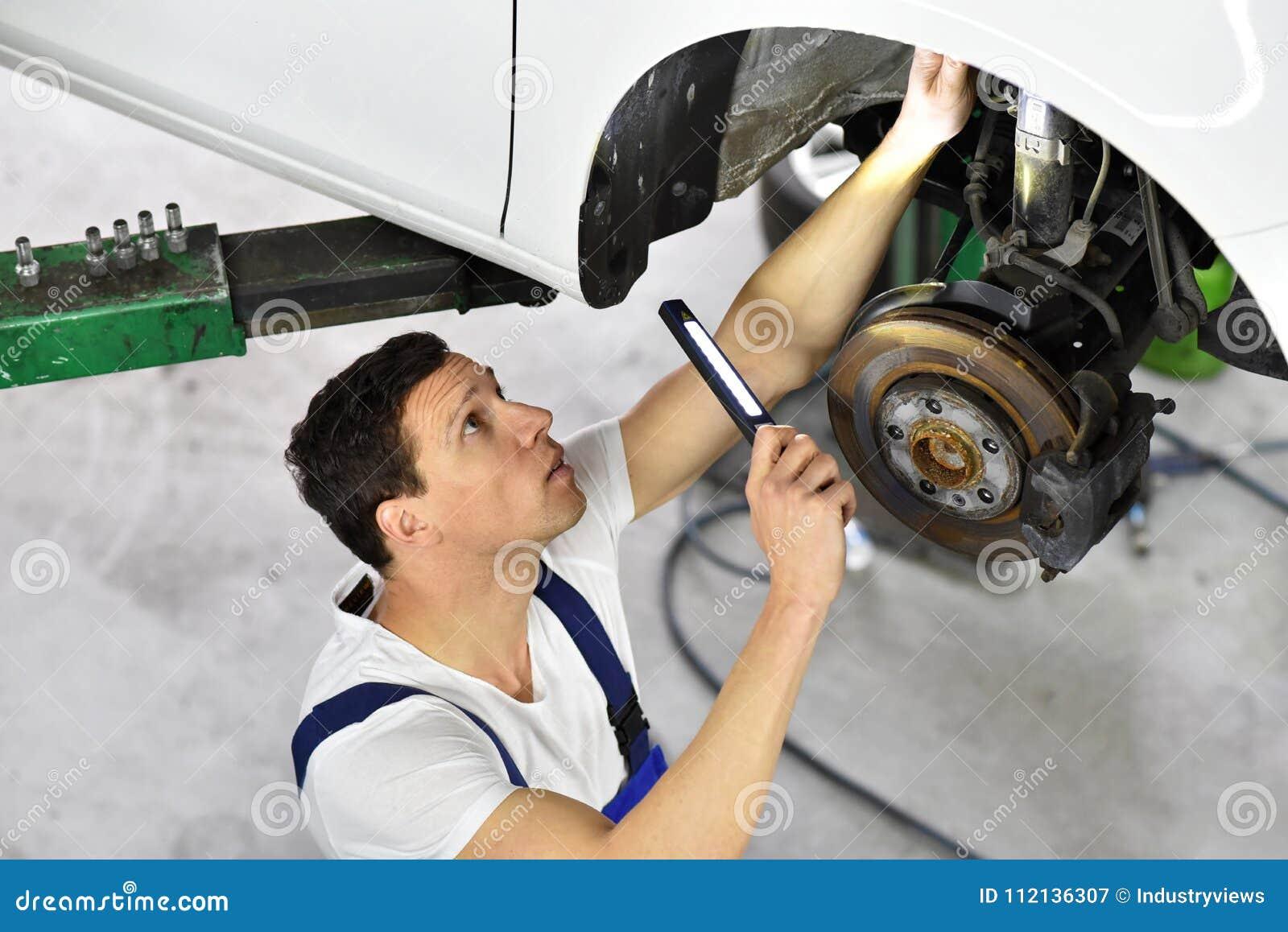 Samochodowy mechanik pracuje w warsztacie, naprawa samochody