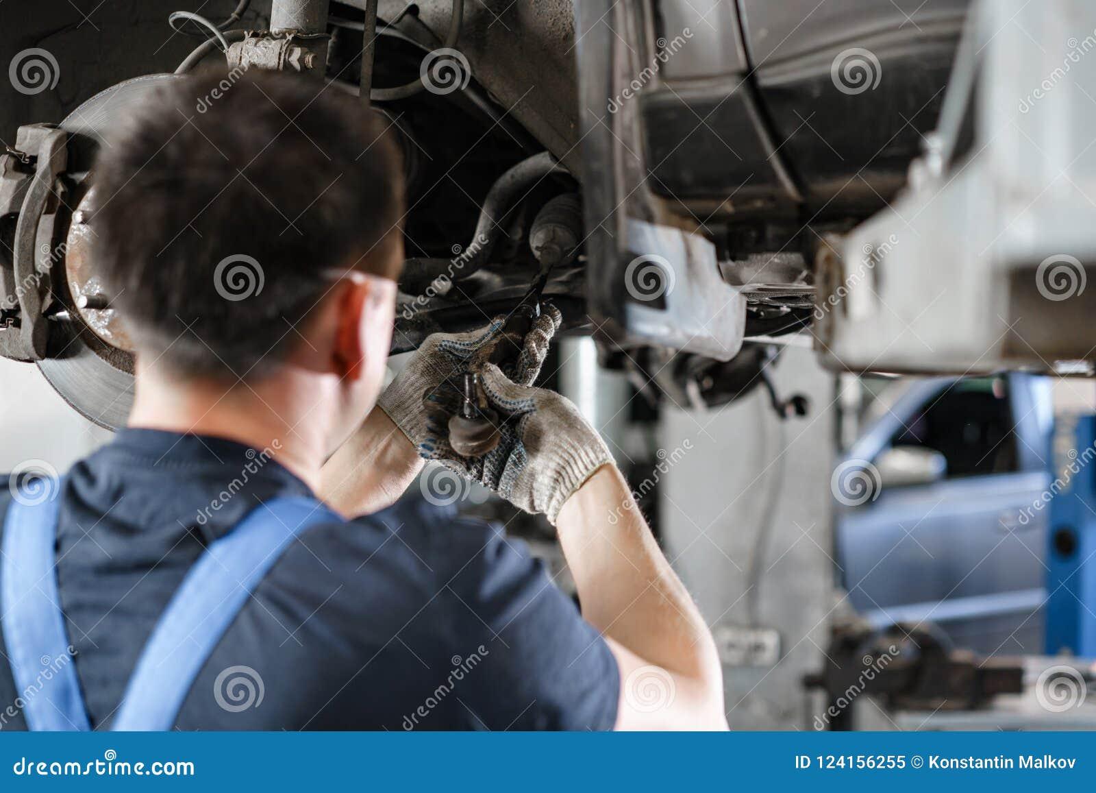 Samochodowy mechanik sprawdza samochodowego koło i naprawy zawieszenia szczegół Podnoszący samochód przy remontową stacją obsługi