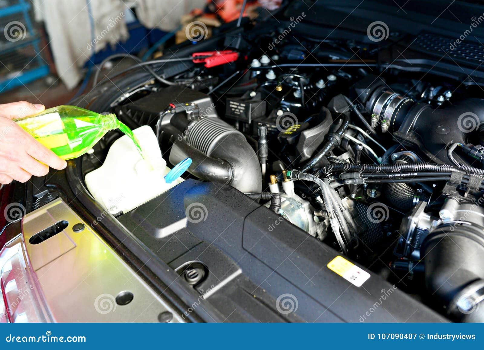 Samochodowy mechanik zmienia coolant na pojazdzie