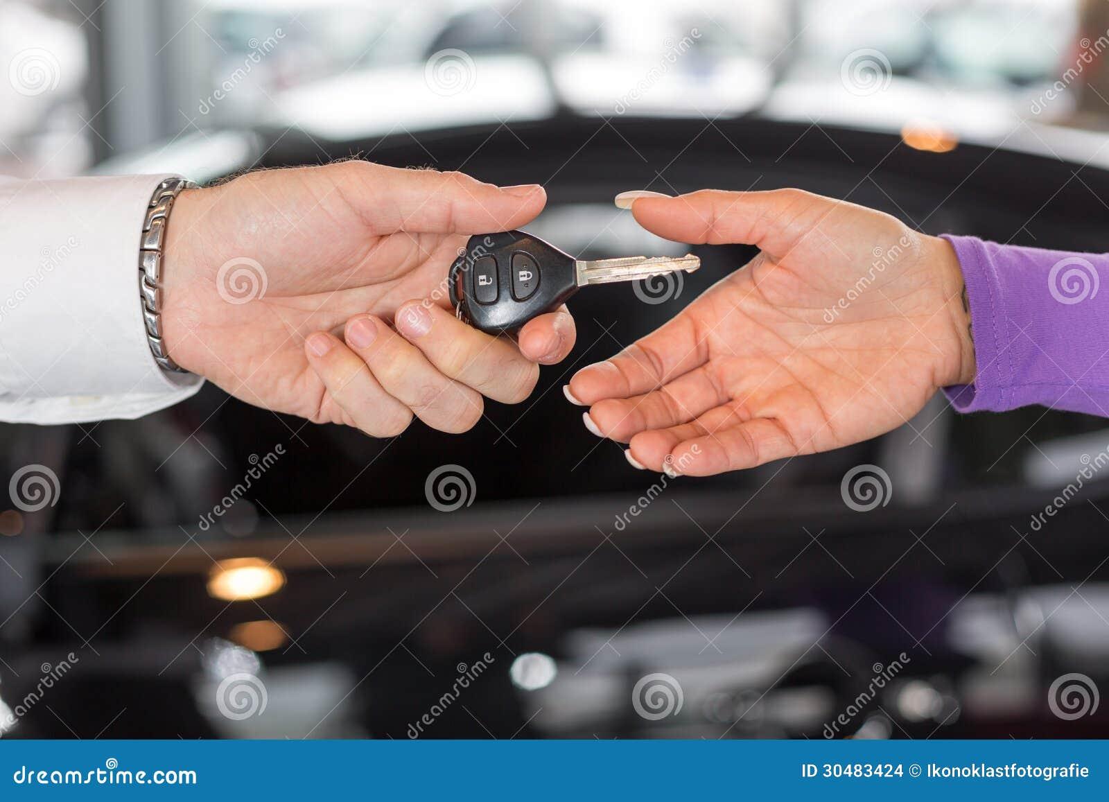 Samochodowy sprzedawca wręcza nad samochodem wpisuje w przedstawicielstwie handlowym