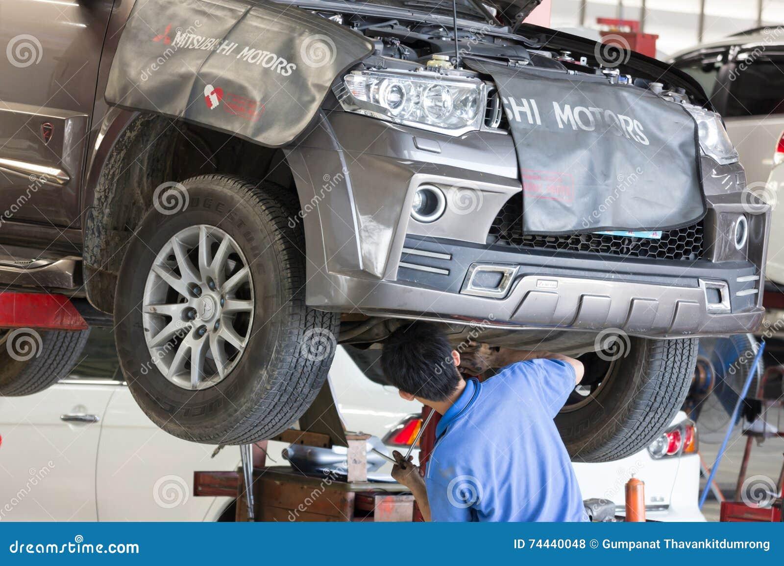 Samochodu mechanik egzamininuje samochodowego zawieszenie podnoszący samochód