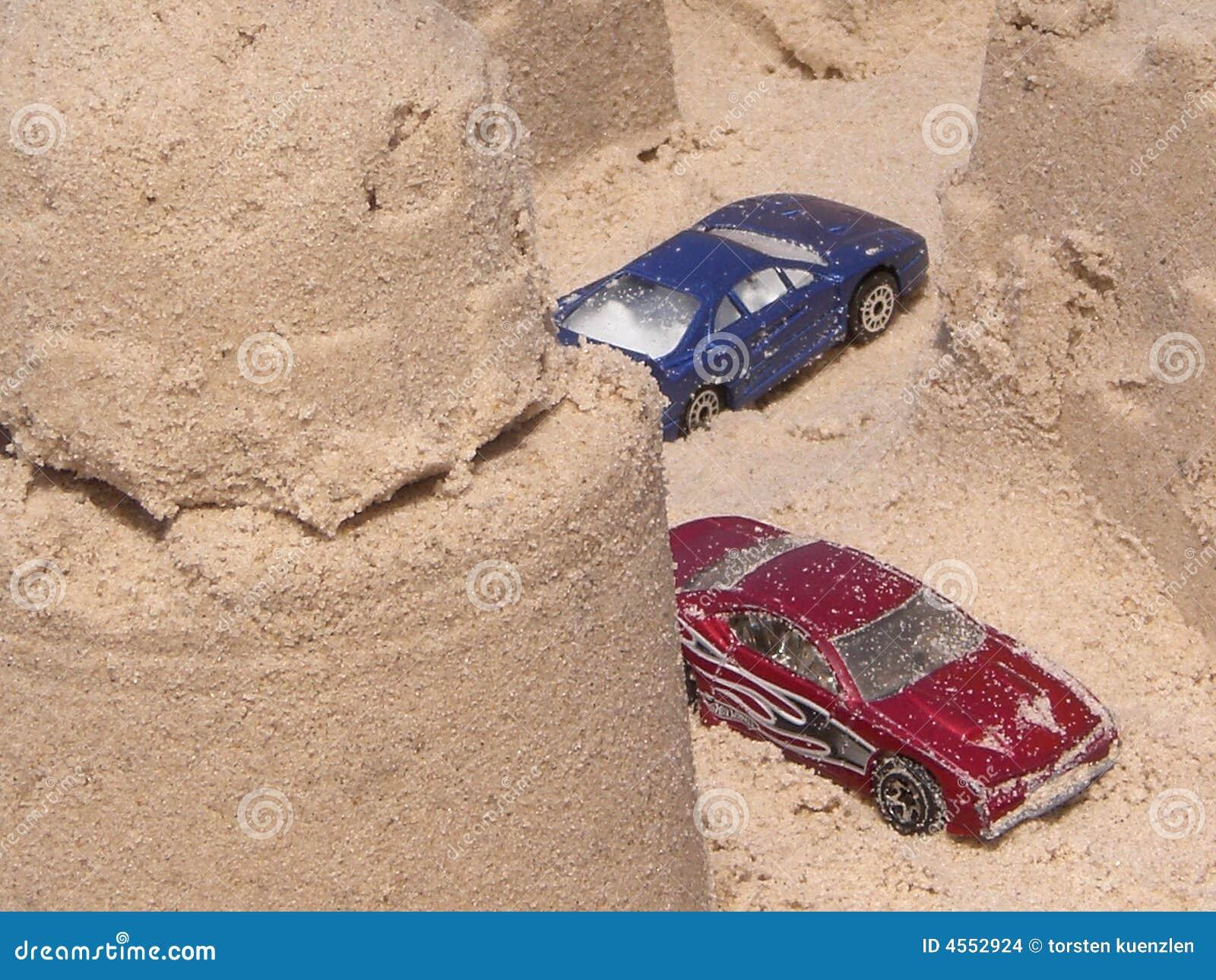 Samochody roszują zabawkę piasek.