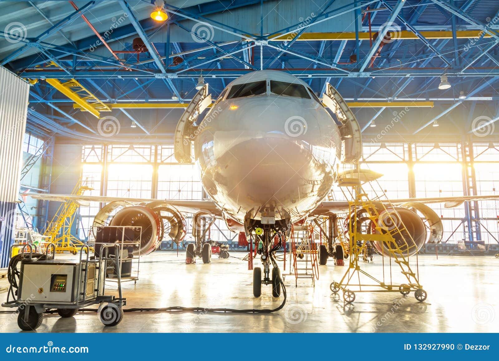 Samolot w lotnictwo przemysłowym hangarze na utrzymaniu, na zewnątrz bramy jaskrawego światła