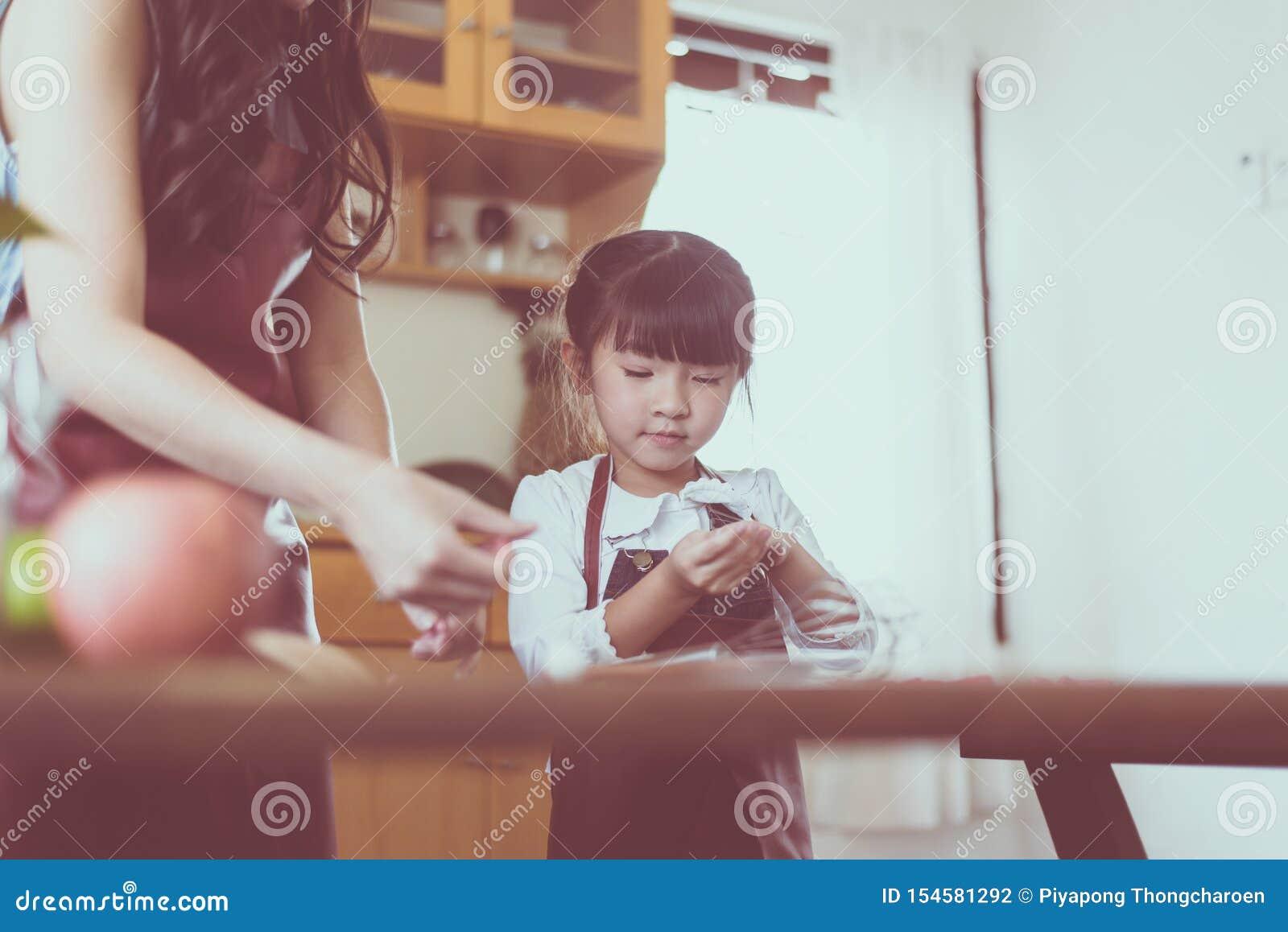 Samotna matka i mała córka robi jedzenie kuchni wpólnie w domu, zakończenie w górę