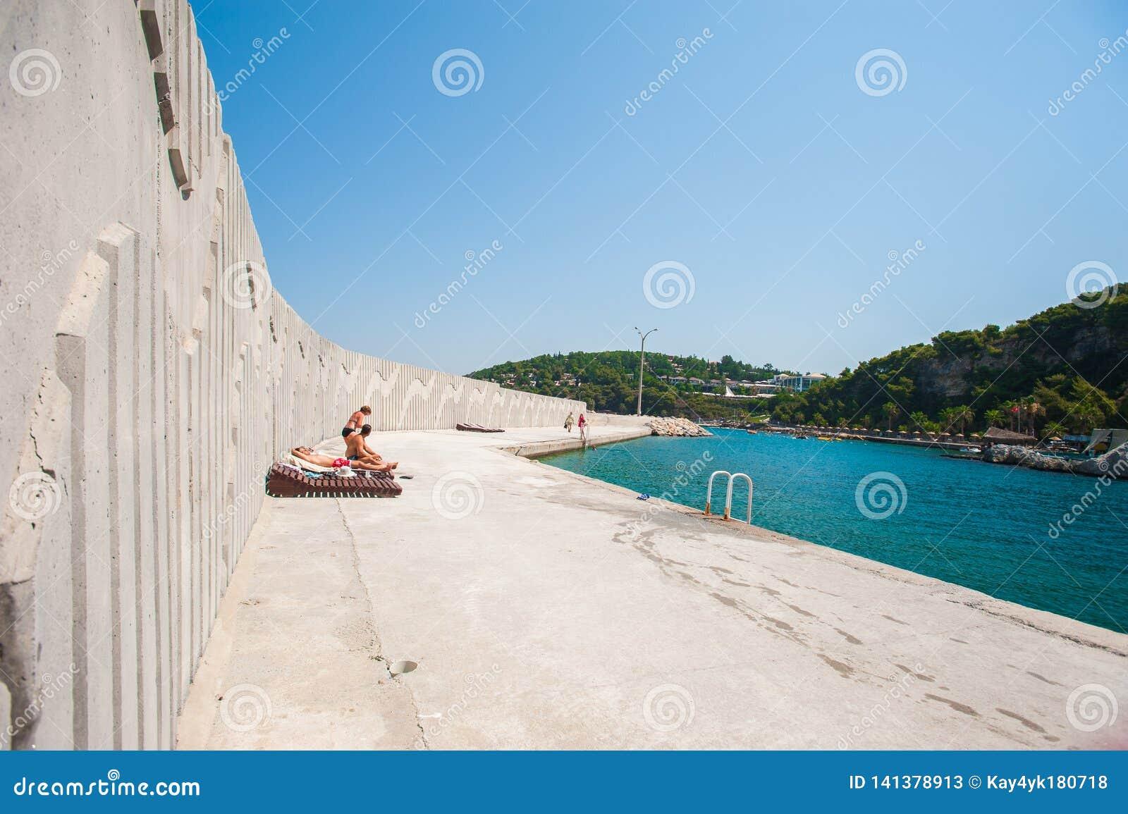 Samotność w odpoczynku, lounger na betonie blisko morza
