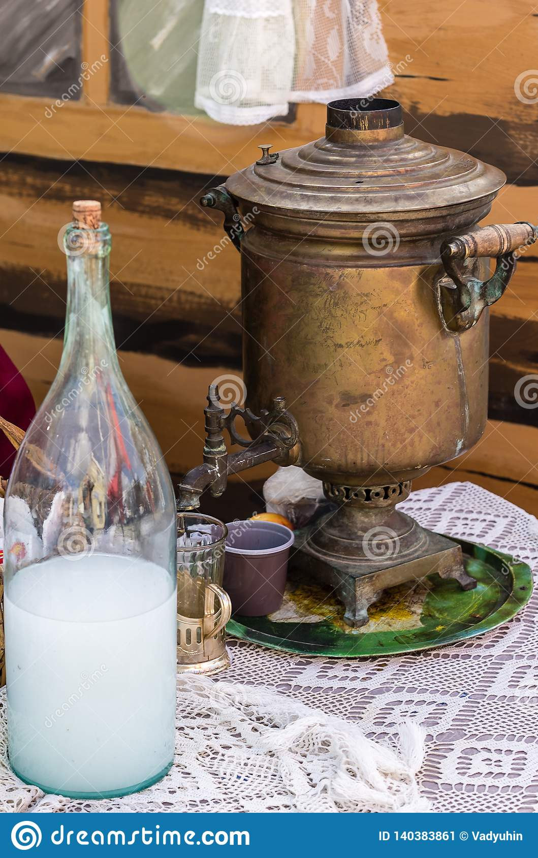 Samovar and moonshine bottle on a lace tablecloth