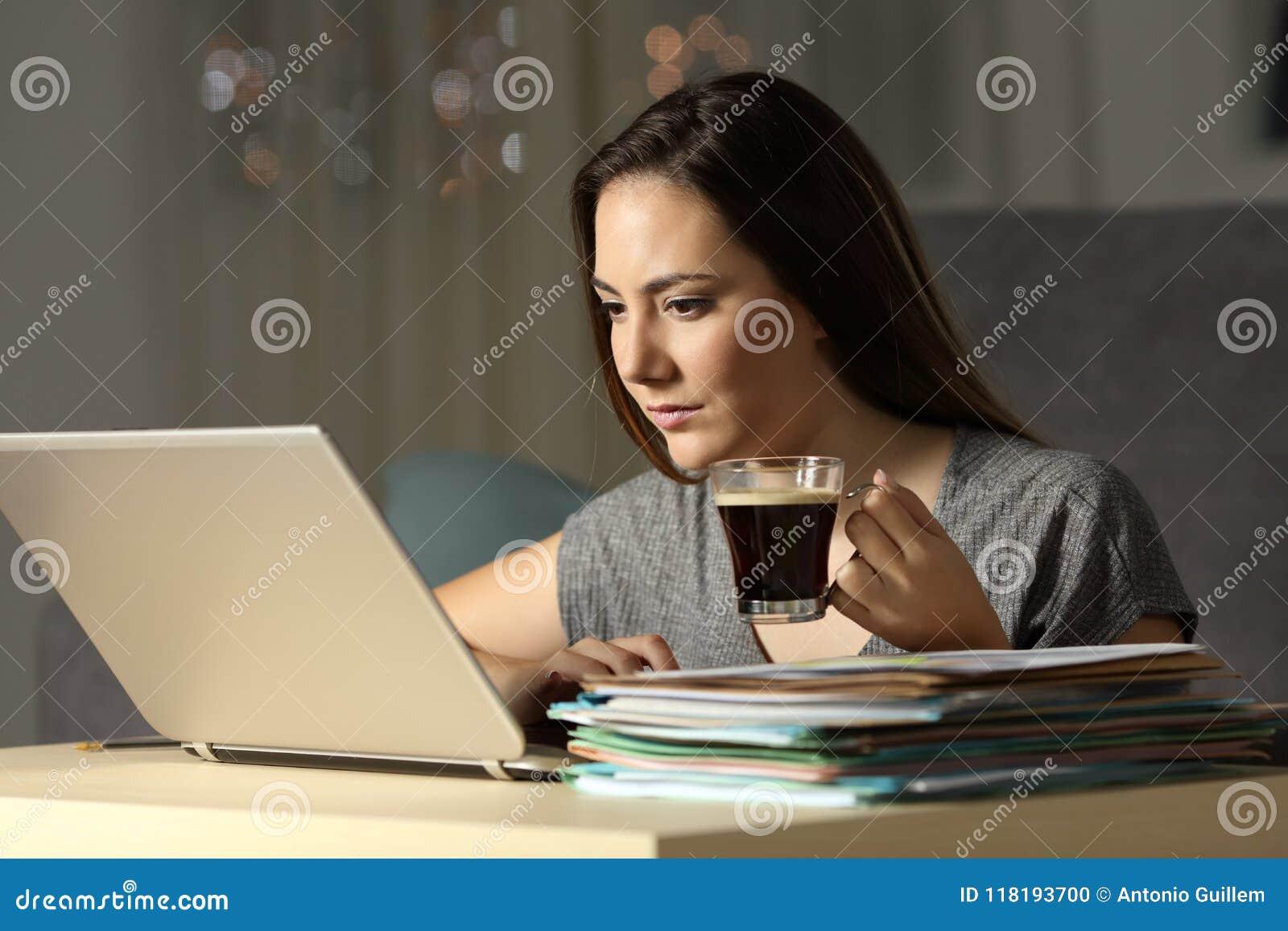 Samozatrudniający się pracujące opóźnione godziny trzyma kawowego kubek