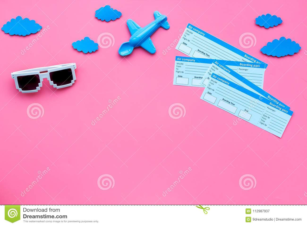 Sample of airplane ticket. Family trip with kid. Airplan toy and sun glasses. Pink background flat lay space for text