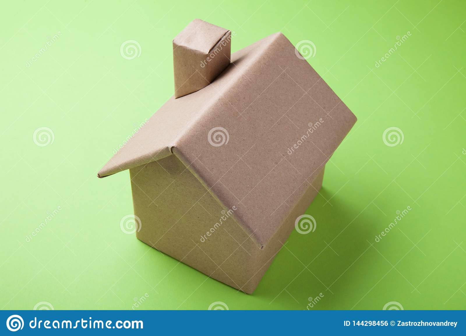 A sample of a dwelling house is made of cardboard. Green background
