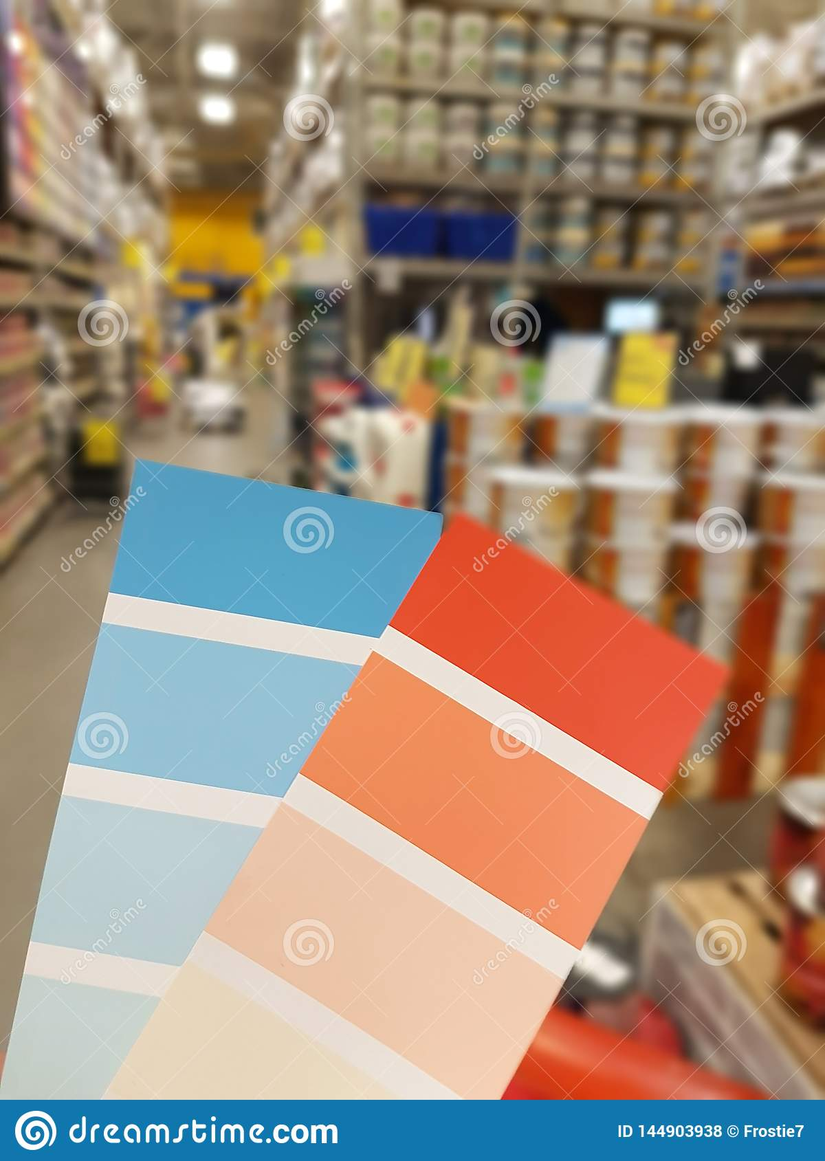 Sample paint blue and orange on the background of cans of paint