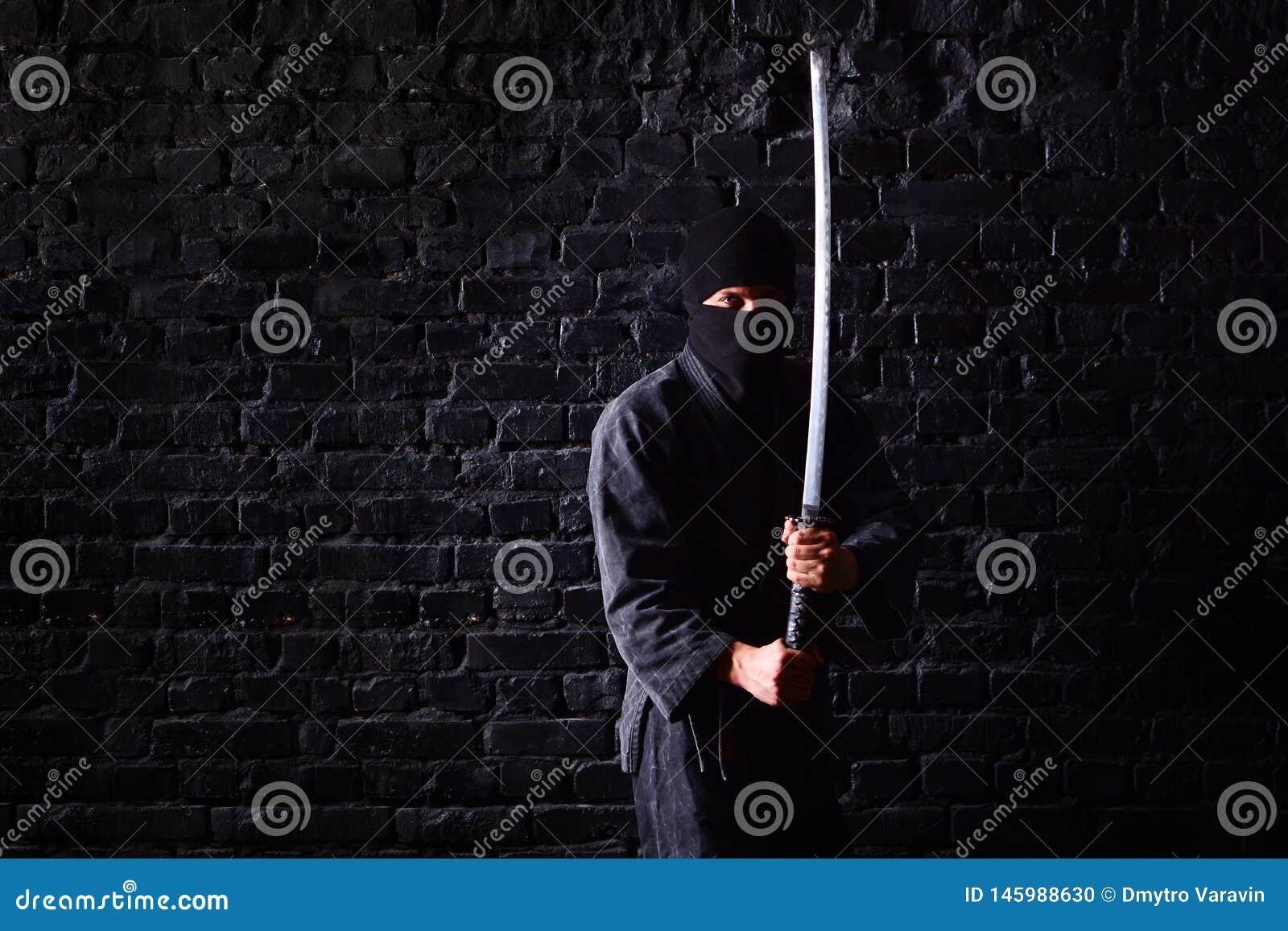 Samurai de Ninja con katana en actitud del ataque en un fondo oscuro de la pared de ladrillo
