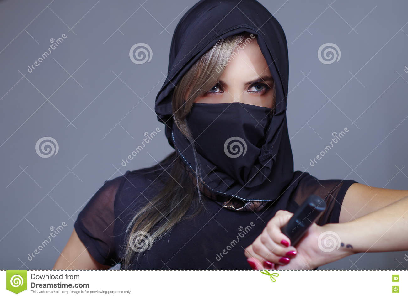 Samurai woman dressed in black with matching veil covering face, holding hand on sword facing camera, ninja concept