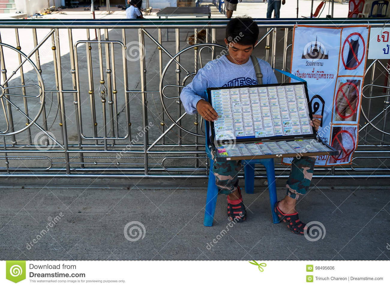 Samutprakarn, Thailand - August 14, 2017 :An unidentified vendor man sitting and holding box of lottery tickets for sale