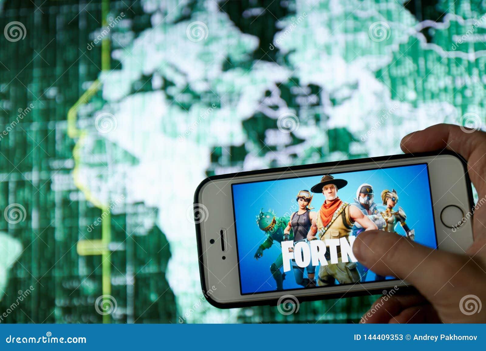 San Francisco, CA los E.E.U.U. - abril de 2019: mano que sostiene un tel?fono con un cierre del logotipo del juego de Fortnite pa
