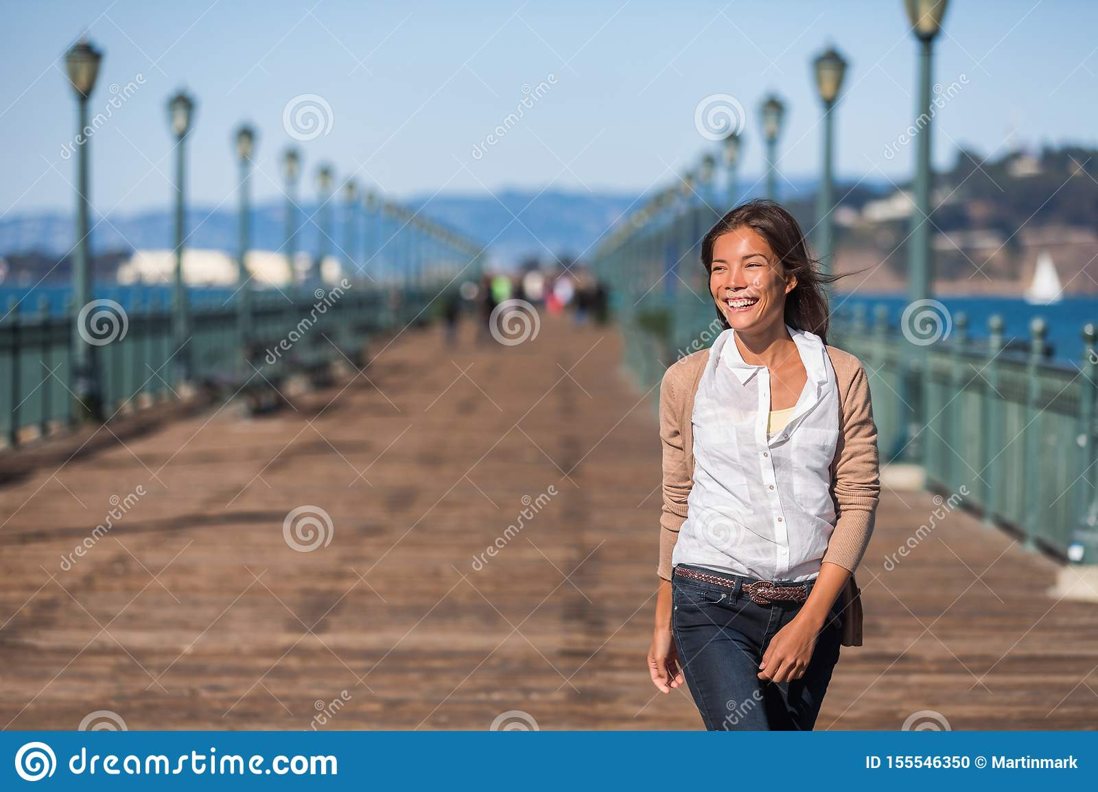 San Francisco travel lifestyle woman walking happy on pier. Asian girl smiling relaxing in harbor city
