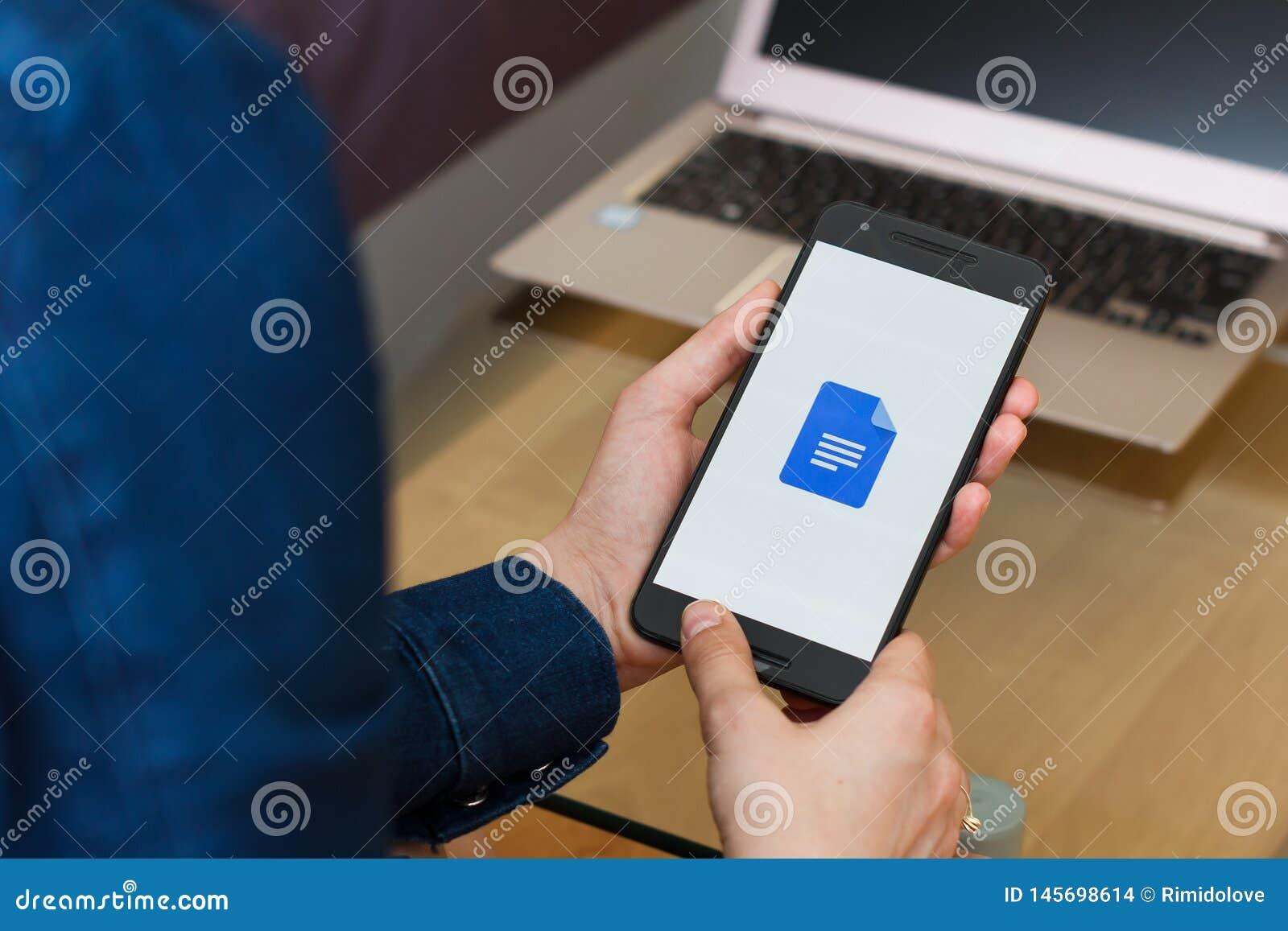 SAN FRANCISCO USA - 22 April 2019: Kvinnliga händer för slut som upp till rymmer smartphonen genom att använda den Google Docs ap