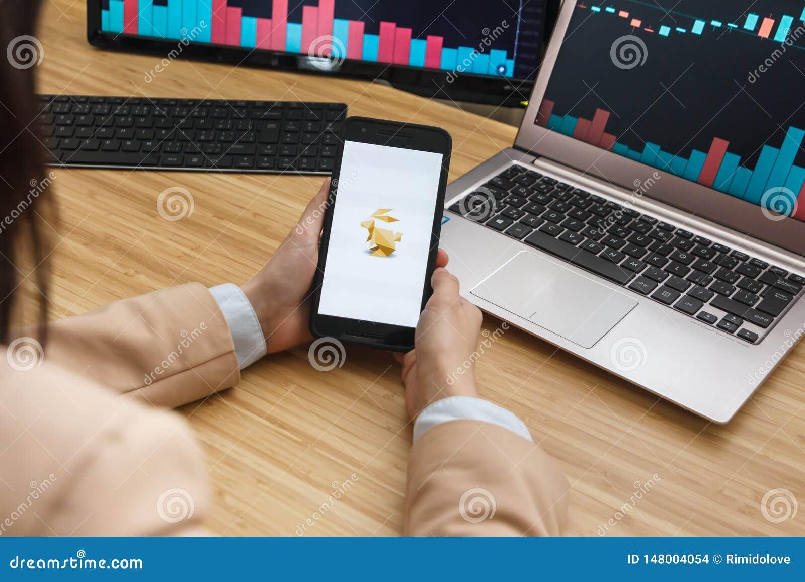 SAN FRANCISCO, USA - 18 mai 2019 : Commerçant féminin Hands Holding Smartphone utilisant l application de l échange de Bitrabbit