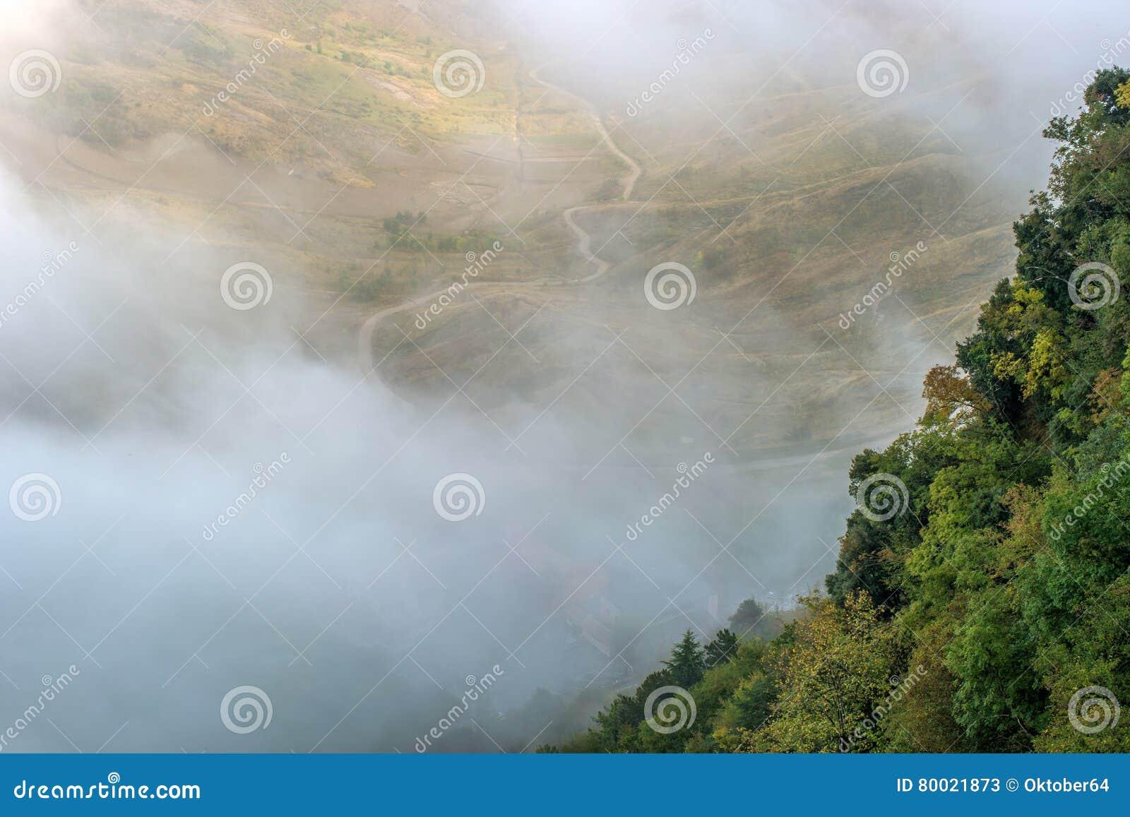 San Marino Italien Lutningen av berget som täckas med träd som döljas i mist