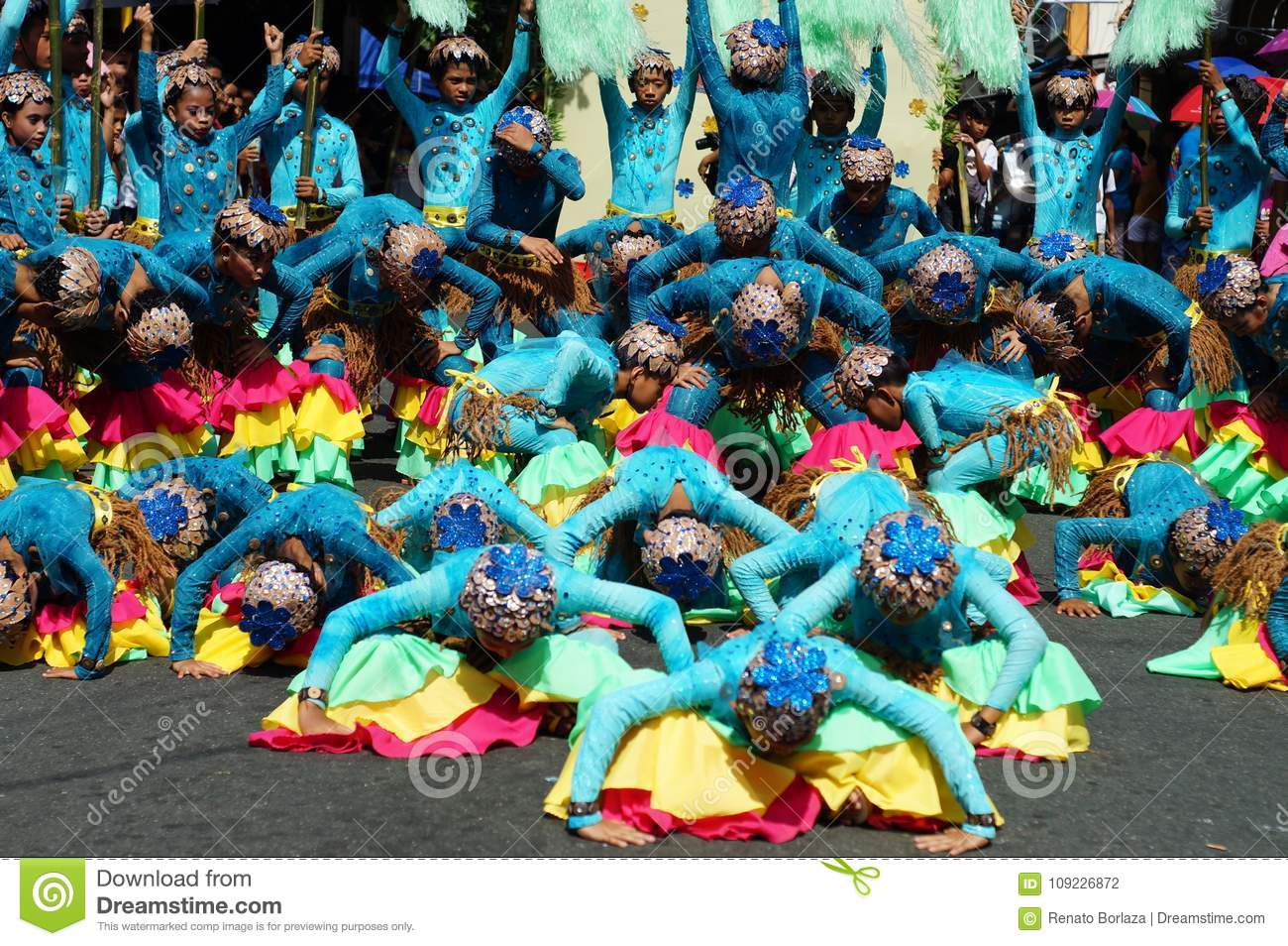 A group of female carnival dancers in various costumes dance along.
