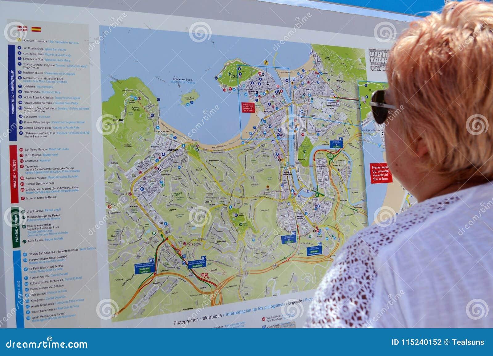 San Sebastian Map Of Spain.Woman Looks At The Map Of Sun Sebastian Editorial Photography