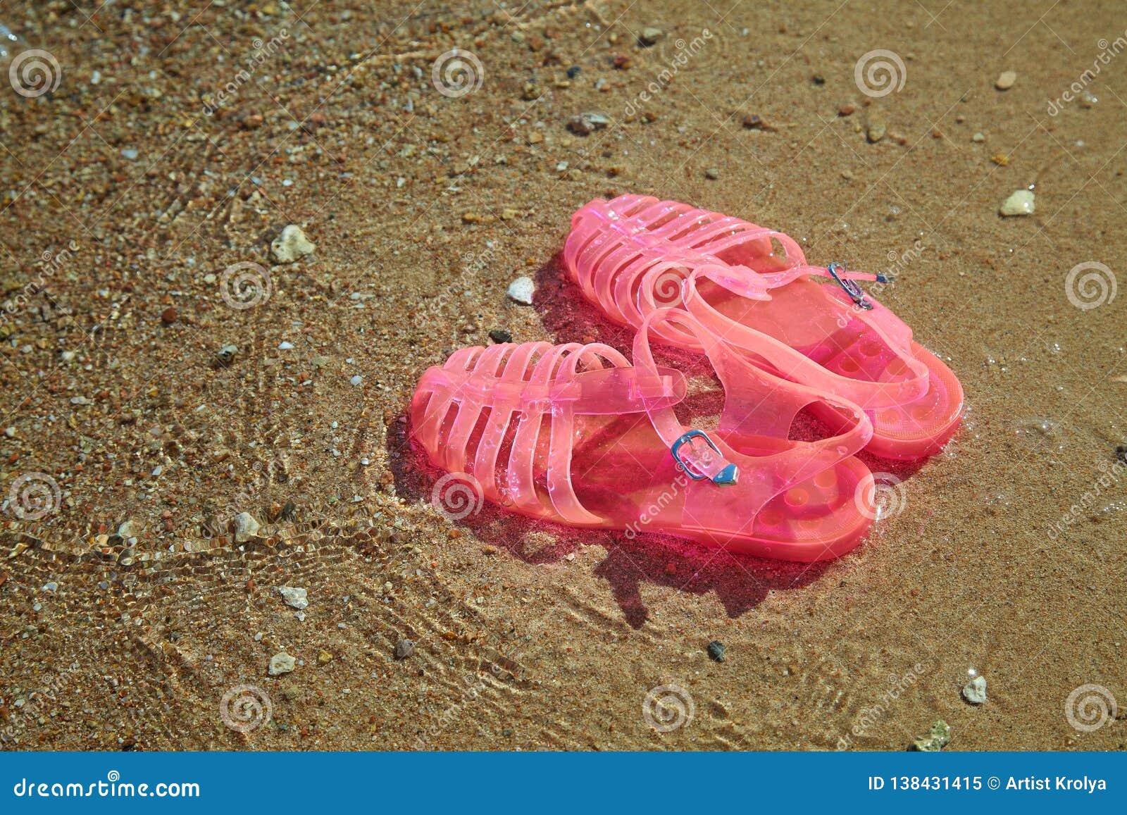 SANDÁLIAS da GELEIA das mulheres cor-de-rosa em uma costa de mar SAPATAS LISAS DA PRAIA DO VERÃO DAS GELEIAS DAS SENHORAS
