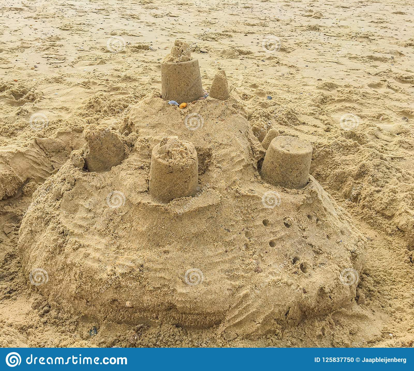 Sand castle construction with towers and shells on the beach sand landscape