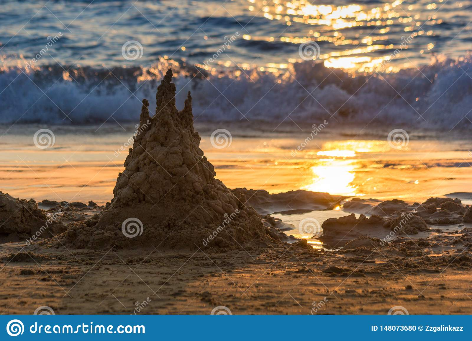 Sand castle is in sunset. Solar track is in the sand. Background