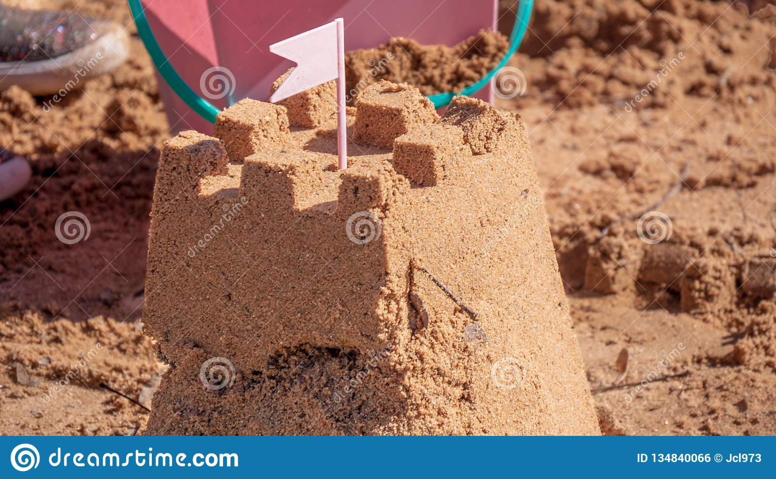 Sand castle surrounded by beach toys