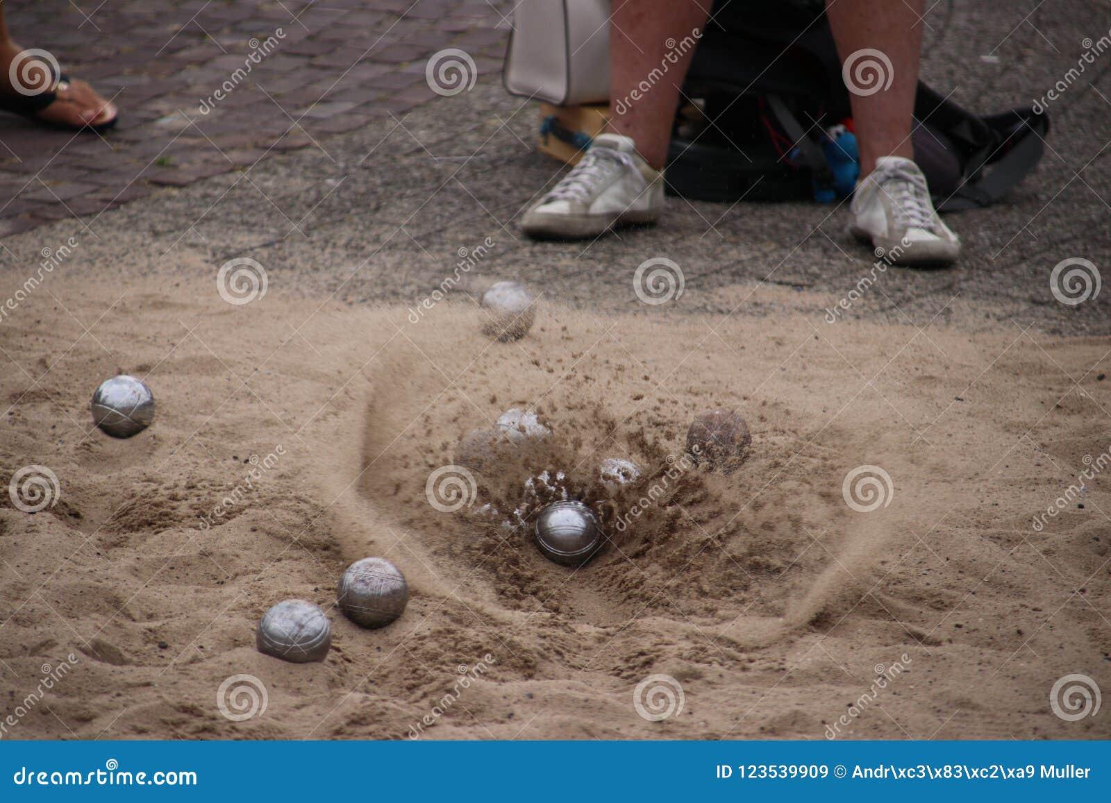 Sand flyger bort, när bollen skulle landa på jordningen under boulesleken