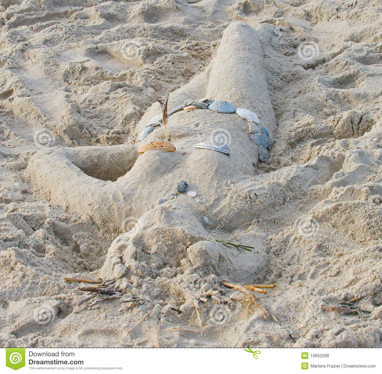 Sand sculpture of a woman with sea shell suit.