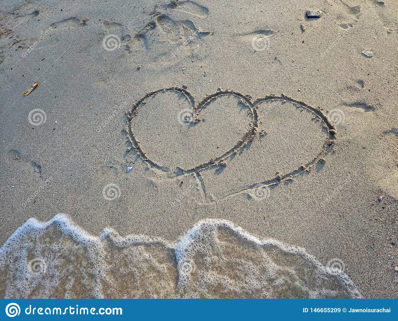 On the sand, there are two hearts drawing. Below is a bubble waves are coming to a little space, summer concept. Valentine concept