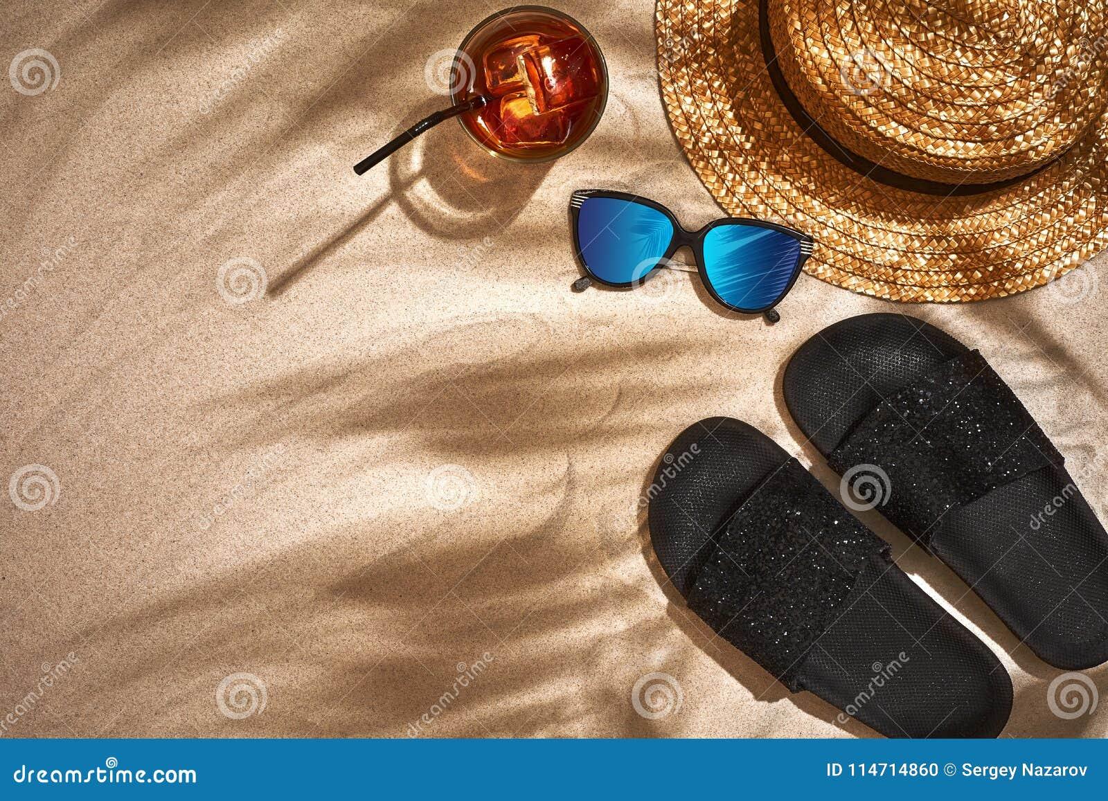 Sandal, sugrörhatt och solglasögon på en sandig bakgrund, bästa sikt