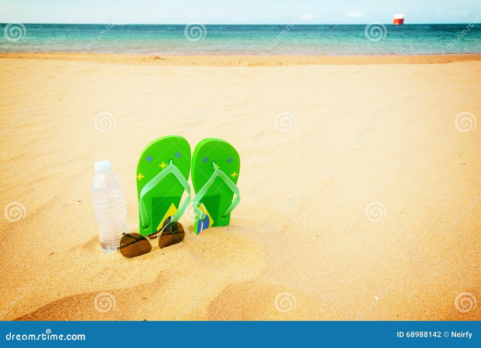Sandalias verdes en la playa arenosa