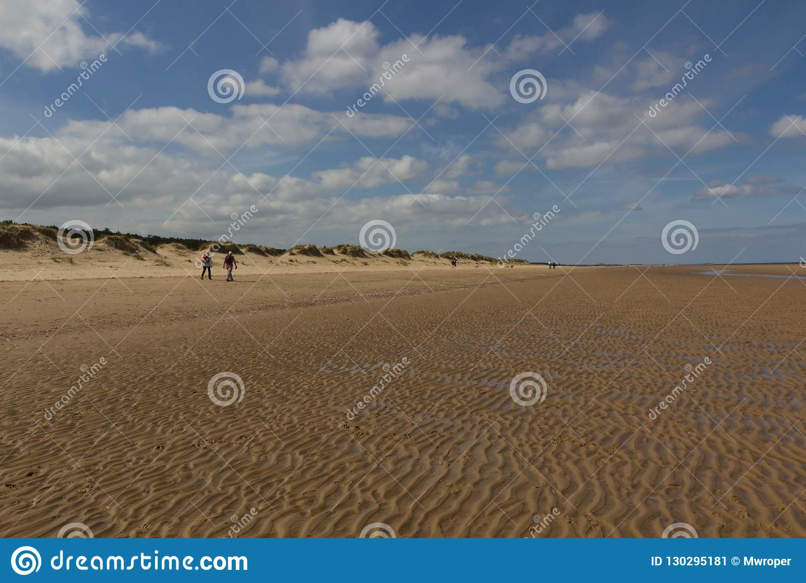Sanddyn och folk som går på stranden på Brunn-nästa--havet