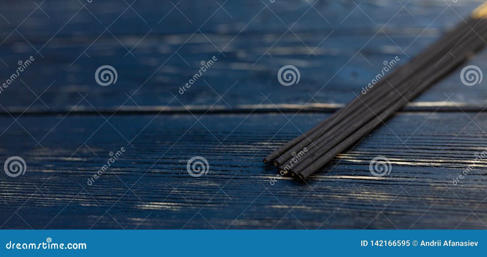 Sandelhoutstokken op een zwarte houten lijst Traditionele Aziatische cultuur Aromatherapy