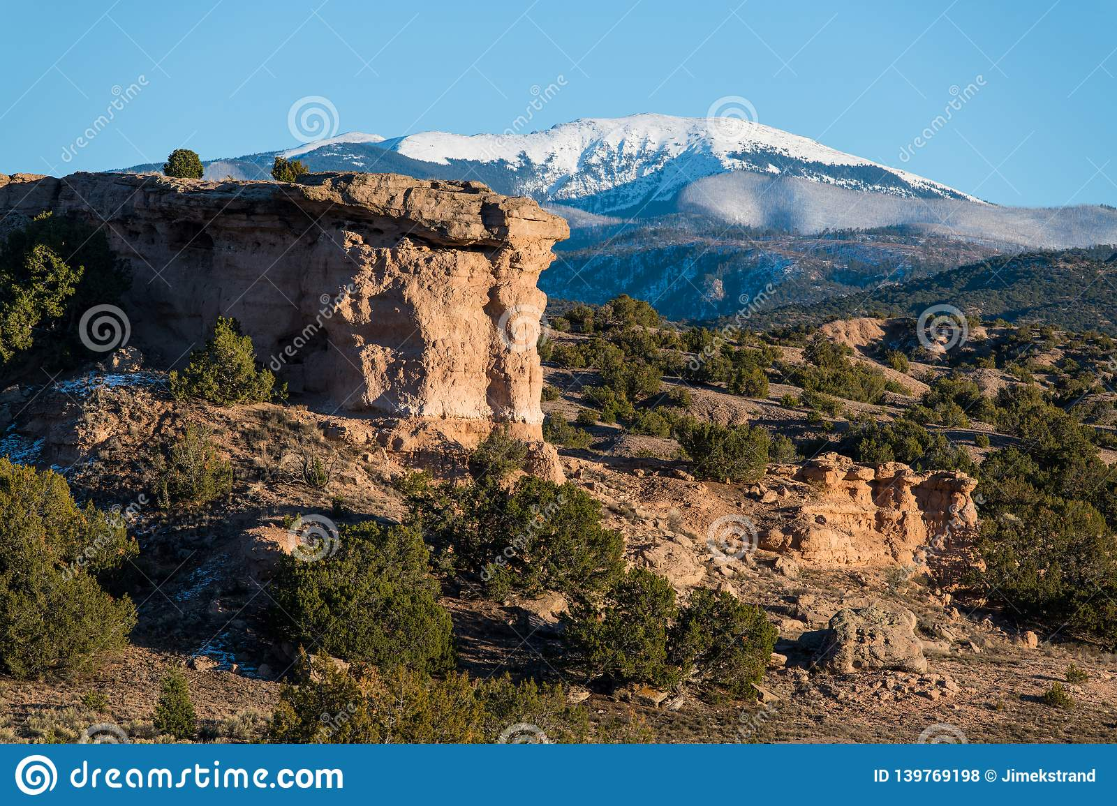 Red rock formation with a snow-capped mountain peak near Santa Fe, New Mexico