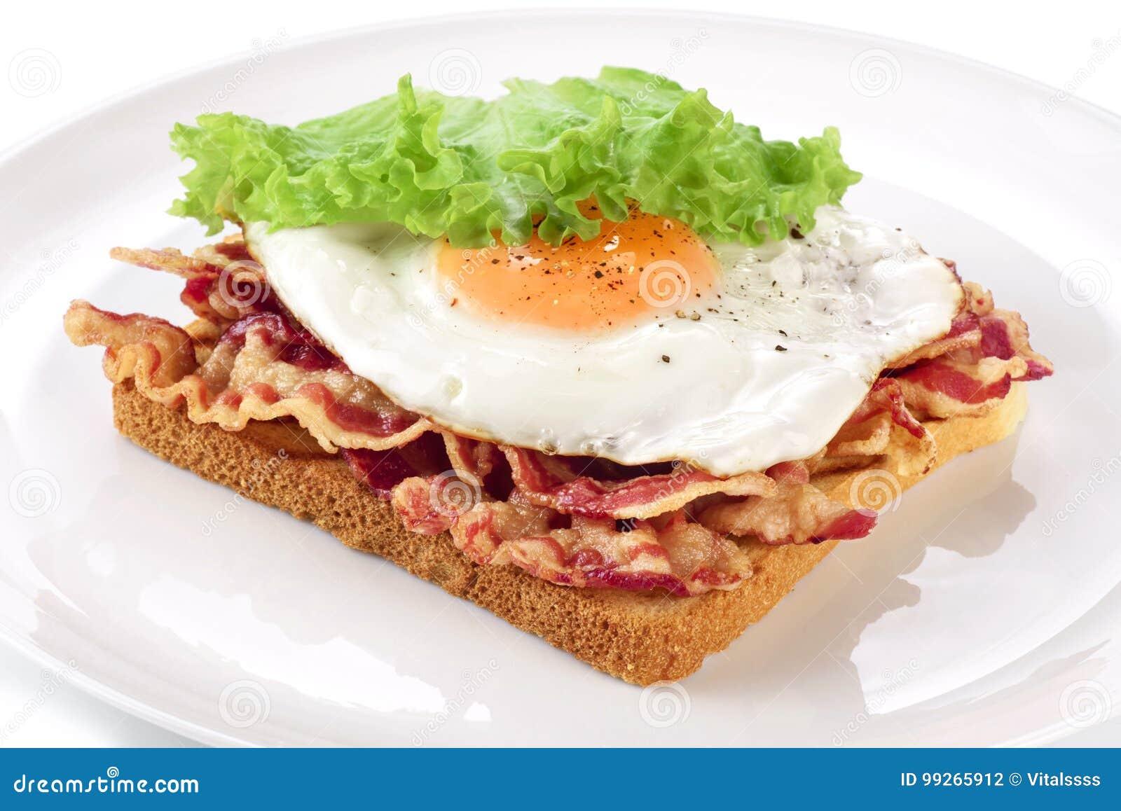 Sanduíche com bacon, ovo frito e alface em uma placa