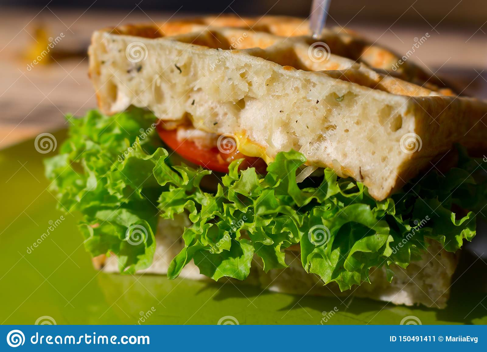Sanduíche de clube saboroso com pão branco do waffle, tomate, cebola, salada na placa verde exterior