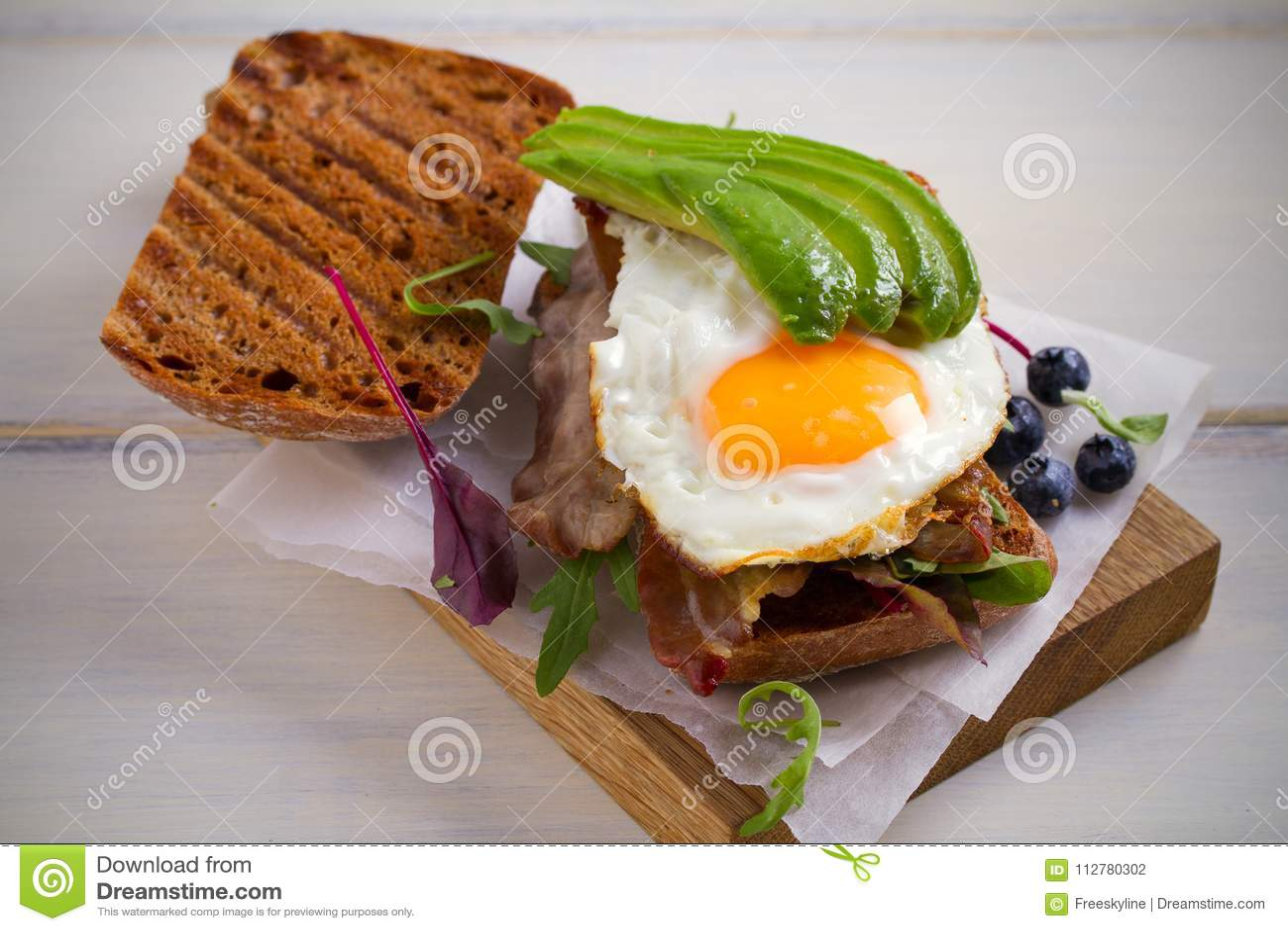 Sanduíche do abacate, do ovo e do bacon Ovo frito e abacate no brinde Panini Alimento saboroso saudável para o café da manhã ou a